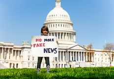 Protester holding sign no more fake news. Child boy protest in front of the USA capitol in Washington holding sign saying no more fake news royalty free stock photos