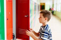 Child boy pulls out clothes from a metal school locker. Child in school royalty free stock image
