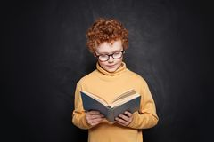 Child boy reading a book on blackboard background in classroom.  royalty free stock images