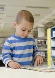 Child boy. Reading a book in a school or public library room stock photos