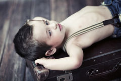 Child boy relaxing on the suitcase Stock Image