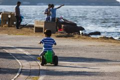 Child boy riding alone at seaside. A child boy is riding his toy alone at seaside in Narlidere Izmir - Turkey stock photography