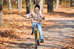 Child boy riding on Bicycle in autumn Park, bright sunny day, fallen leaves on background Stock Photos