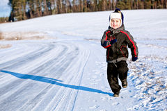 Child Boy Running Along The Road In Winter Stock Photo