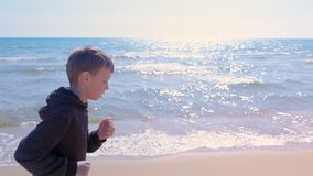 Child boy is jogging on sea sand beach little runner sport outdoors side view.