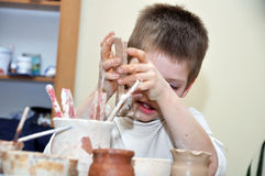 Child  boy shaping clay in pottery studio Royalty Free Stock Image