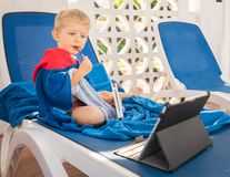 Child boy is sitting on the beach chairs and eats and looks the tablet in front of him royalty free stock photos
