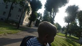 Child boy sitting on bicycle chair while driving and looking around. Child boy sitting on bicycle chair stock video