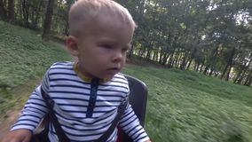 Child boy sitting on bicycle chair while driving and looking around. Child boy sitting on bicycle chair stock video footage