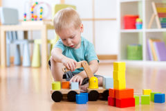 Child boy sitting on the floor and plays with building blocks and car. Indoor Royalty Free Stock Photos
