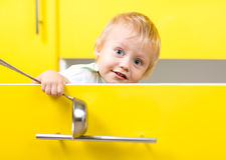 Child boy sitting inside opened kitchen box and Stock Photos