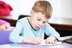 Child boy studying writing. Child education. boy studying writing at the classroom royalty free stock image