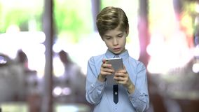 Child boy surfing internet on digital smartphone. Cute caucasian boy watching video on mobile phone. Abstract blurred background stock video footage