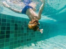 A child boy is swimming underwater in a pool, smiling and holding breath, with swimming glasses.  royalty free stock images