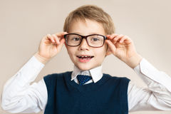 Child boy teenager with glasses on a gray background. Objects over white. Funny child. Portrait of handsome smiling little smart schoolboy in glasses Royalty Free Stock Photos