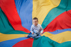 Child boy toddler sitting in the center of playground rainbow parachute. Portrait of white Caucasian child boy toddler sitting in the center of playground royalty free stock photo