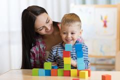 Child boy together with mother playing toys Stock Photography