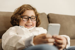 Child boy using his mobile phone. Royalty Free Stock Photography