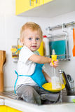 Child boy washing dishes and having fun in the Stock Images