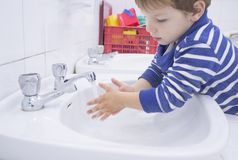 Child boy washing hands at adapted school sink. Learning hygiene habits stock photography