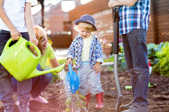 Child boy watering plant with his mother and brothers in garden Royalty Free Stock Images