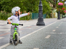 Child boy in white helmet riding on his first bike with a helmet. Bike without pedals. Royalty Free Stock Photography