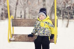The child. boy in winter clothes riding on a swing, emotion, laughing, winter, snow royalty free stock photos