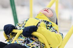 The child. boy in winter clothes riding on a swing, emotion, laughing, winter, snow royalty free stock images