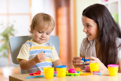 Child boy and woman play colorful clay toy at. Child kid boy and mother play colorful clay toy at nursery or kindergarten Royalty Free Stock Photo