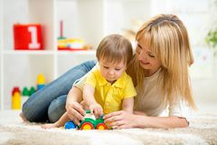 Child boy and woman playing with toy indoor. Child boy and women play with toy indoor Royalty Free Stock Image