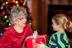Child bringing Christmas present to Grandmother Royalty Free Stock Photography