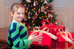 Child bringing Christmas presents with tree Royalty Free Stock Image
