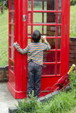 Child by a Brithish phone box royalty free stock photos