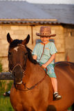 Child on brown horse royalty free stock photo