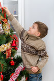 Child in brown sweater hangs Christmas toy Royalty Free Stock Photo