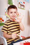 Child with brush draw red sun in play room. Royalty Free Stock Photo