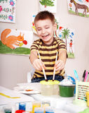 Child with brush painting picture in play room. Royalty Free Stock Images