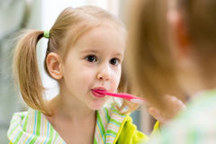 Child brushes teeth looking at mirror in bathroom Royalty Free Stock Photos