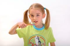 Child brushing his teeth isolated on white