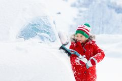 Child brushing off car. Kid with winter snow brush stock photography