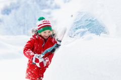 Child brushing snow off car after storm. Kid with winter brush and scraper clearing family car after overnight snow blizzard. Family Christmas vacation in the royalty free stock photos