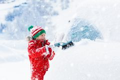 Child brushing off car. Kid with winter snow brush. Child brushing snow off car after storm. Kid with winter brush and scraper clearing family car after royalty free stock photography