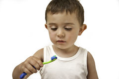 Child brushing teeth. Portrait of a young toddler looking at his toothbrush and preparing to brush his own teeth isolated on a white background stock photos
