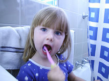 Child Brushing Teeth. Young child brushing her teeth in the bathroom Royalty Free Stock Image
