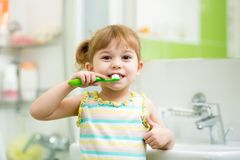 Child brushing teeth in bathroom Stock Images