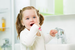 Child brushing teeth in bathroom Royalty Free Stock Images