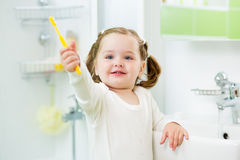 Child brushing teeth in bathroom Stock Image