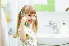 Child brushing teeth in bathroom Stock Photos