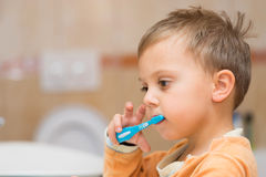 Child is brushing teeth in bathroom royalty free stock image