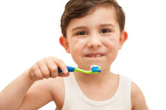 Child brushing teeth isolated. Child brushing his teeth. There is toothpaste on the toothbrush and he has two new adult teeth. He is wearing a vest and this is stock photo